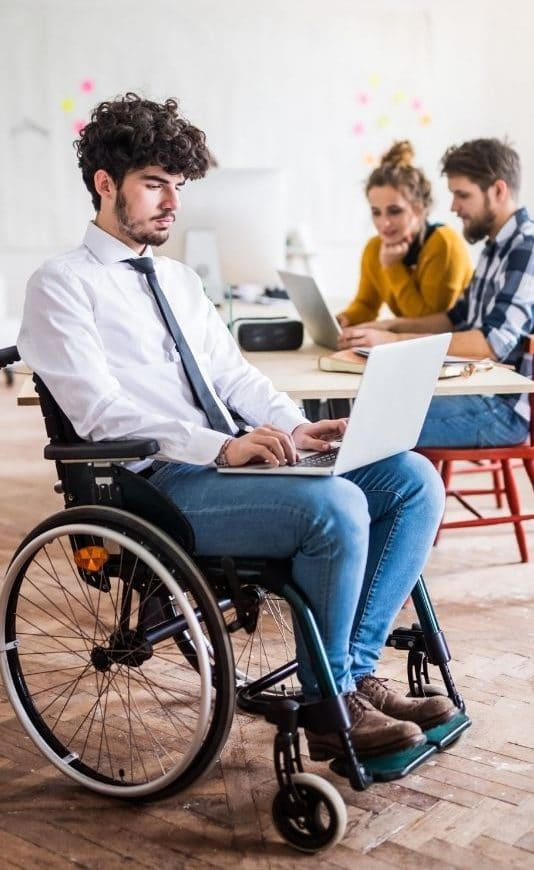 temporary staffing services: man in wheelchair working on computer while coworkers are working behind him at a table